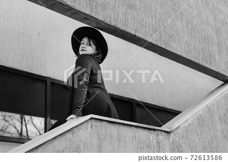 Brunette woman in hat on the stairs of building in city. Plus size model 72613586