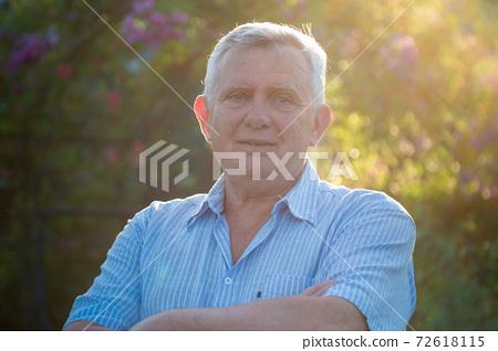 Happy senior man in light blue shirt in sunny garden 72618115