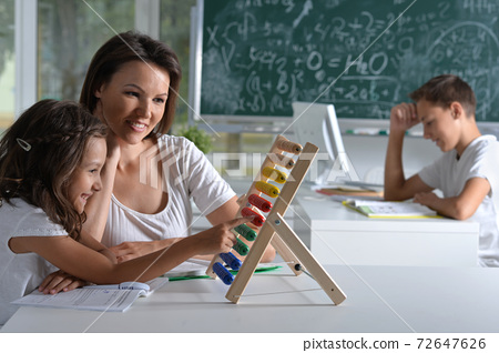 Woman teaching girl to use abacus indoors 72647626