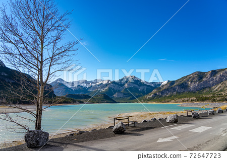 Barrier Lake Dam lakeshore in autumn season sunny day morning. Snow capped mountains in with blue sky in the background. kananaskis, Alberta, Canada. 72647723