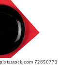 Black plate on a red napkin isolated on white background 72650773