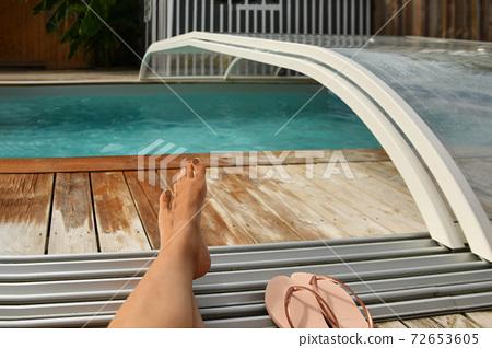 Woman legs near the outdoor pool Summer 72653605