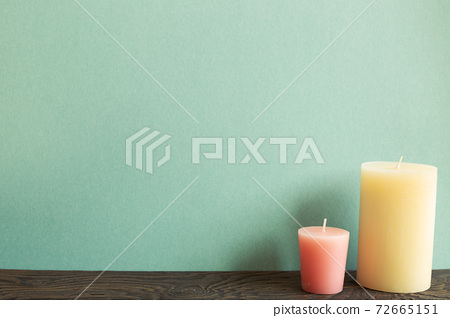 Color candles on wooden table. green background 72665151