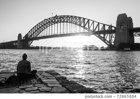Lady contemplating the sun setting behind Harbour bridge 72665884