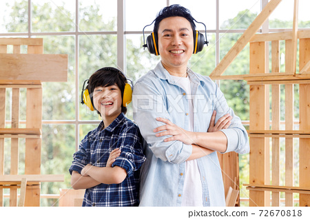 Happy Asian father and son wearing ear muffs and standing in carpentry workshop. 72670818