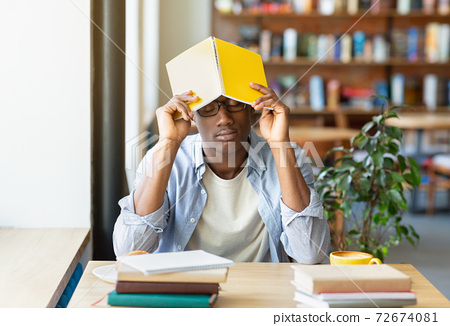 Overworked black guy sleeping during his studies at city cafe, putting book on his head, tired of doing home assignment 72674081