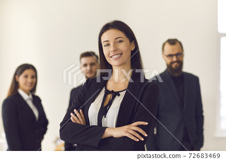 Portrait of a smiling pretty young business woman on the background of employees. 72683469