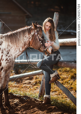 Beautiful young girl posing with her horse in the nature. Sunny autumn day. 72685784