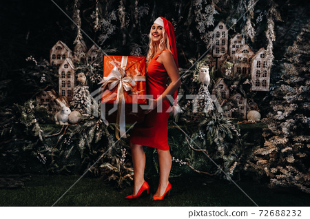 a girl in a Santa hat with a big Christmas gift in her hands on a fabulous Christmas background.A smiling woman in a red dress on the background of Christmas trees and small houses 72688232