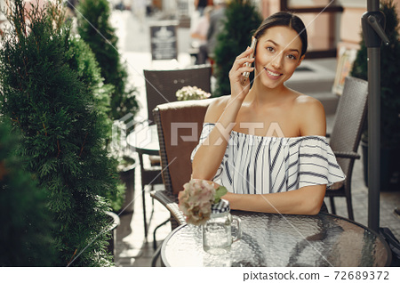 Fashion young girl in a summer cafe 72689372