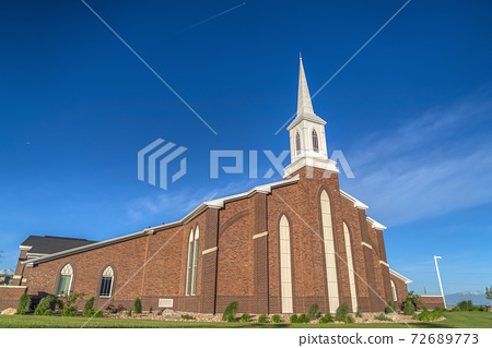 Sunny day view of a church with white steeple and vibrant blue sky background 72689773