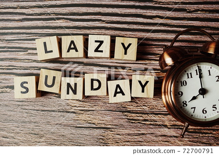Lazy Sunday alphabet letter with alarm clock on wooden background 72700791