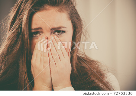 Sad woman cover face with hands 72703536