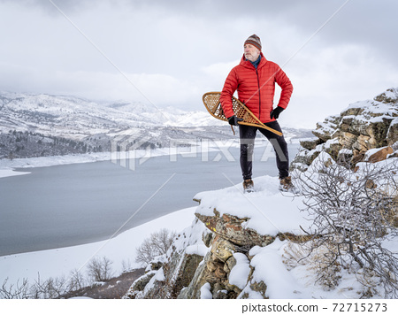 senior man with classic Huron snowshoes is overlooking a mountain lake 72715273