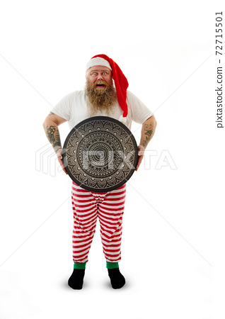 Isolated full-length portrait on a white background of an overweigh funny shaman with tattooed arms in Santa Claus hat holding a shaman tambourine with beautiful luxury mandala ornament. 72715501
