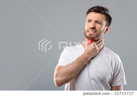 Sick man having sore throat, looking at copy space 72715717