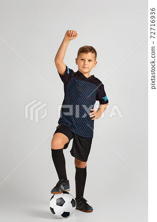 little boy football player in uniform holding ball 72716936