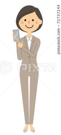 有一套衣服的一名婦女與智能手機 72737244