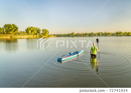 male paddler with stand up paddleboard 72741934