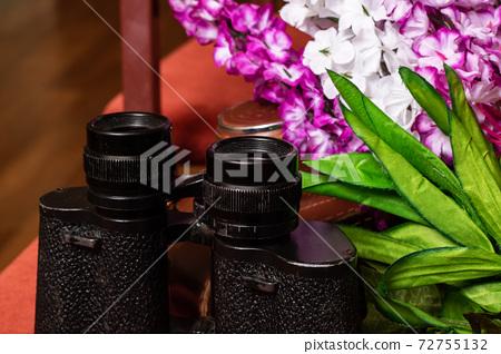 Black binoculars on the background of flowers 72755132