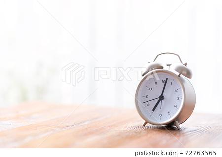창가의 책상 위에 놓인 아침에 비춰지는 알람 시계 72763565