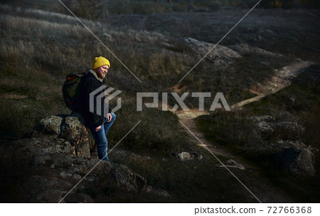 Side full-length portrait of a male traveller in yellow hat with a backpack on his back sitting on a rock on background of a walkway. Concept of people traveling in nature. 72766368