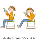 A woman sitting on a chair and using a smartphone 72770432