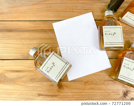 A little bottle of honey to make a souvenir and a mock up white card is placed on a wooden table. 72771200