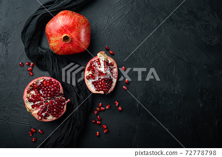 Ripe pomegranate with fresh juicy seeds, on black textured background, flat lay with space for text 72778798