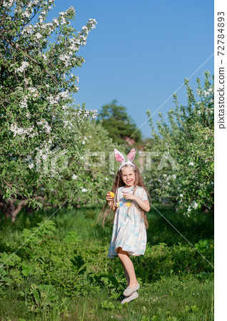 Cute girl with bunny ears on Easter day. A girl is chasing Easter eggs in the garden. 72784893