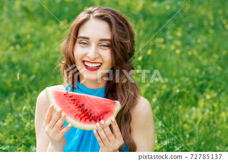 Portrait of smiling girl with slice of watermelon on background of green grass. 72785137