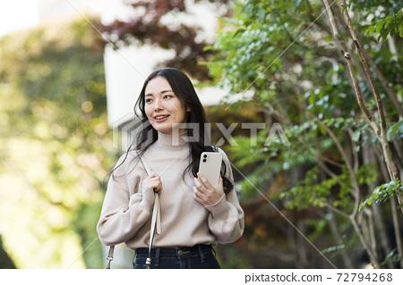 스마트 폰을 가지고 걷는 젊은 여성 72794268