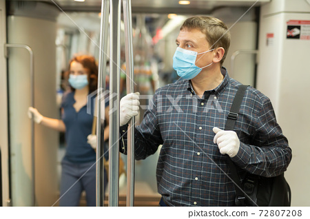Man in medical mask riding in subway car 72807208