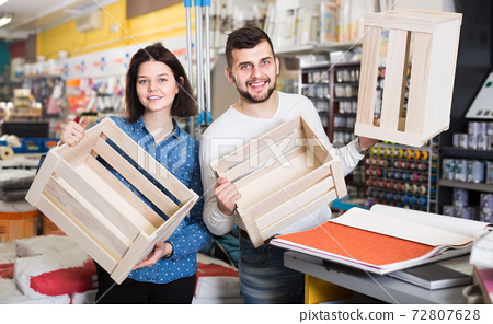 Young loving couple demonstrating boxes for decorating house in paint store 72807628