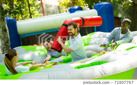 Team of friends playing with inflatable sticks on the trampoline 72807767