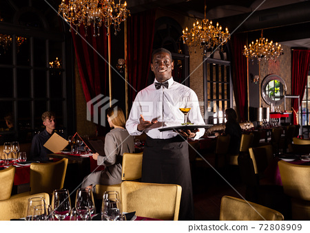 Hospitable african-american waiter standing with serving tray meeting restaurant guests 72808909