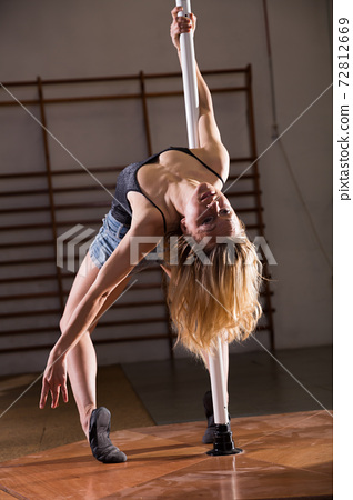Young woman in denim shorts practicing pole dancing 72812669
