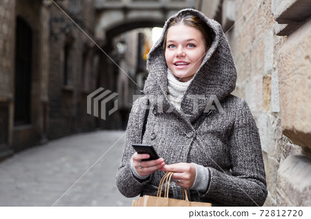 young female with mobile in hood 72812720