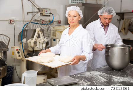 Woman preparing formed dough for proofing 72812861