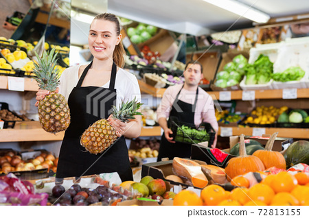 Young saleswoman wearing apron showing pineapples on the supermarket 72813155