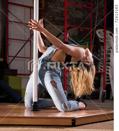 Young woman in ripped jeans performing pole dance 72813165