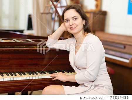 Attractive young woman chooses pianoforte in a record store 72814451
