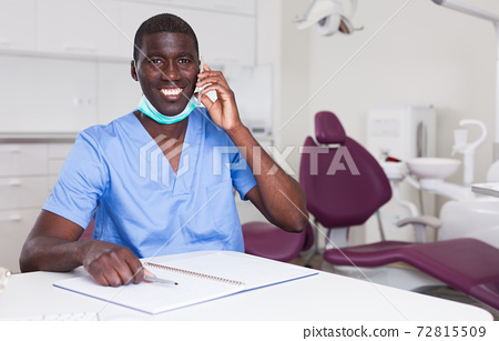 Dentist african american talking on mobile phone in office 72815509