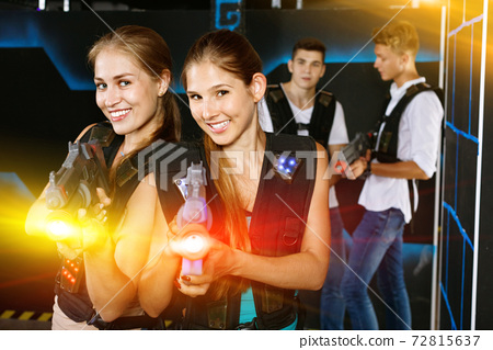 Two smiling girls posing with plastic laser pistols and two guys 72815637