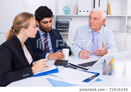 Employees are working together at computer 72816249