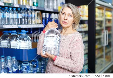 Portrait of casual woman choosing bottled water 72817466