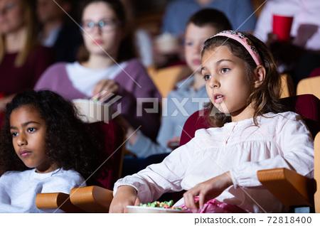 Tween girl with aframerican friend watching movie in cinema 72818400