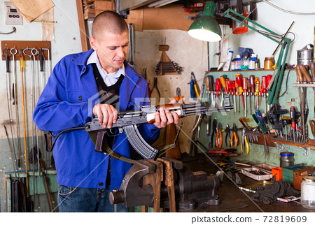 Gunsmith performing maintenance of Kalashnikov assault rifle in workshop 72819609