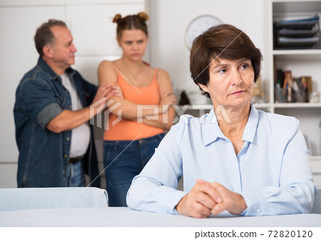 Man and his daughter are sympathying their sad mother who is sitting at the table 72820120