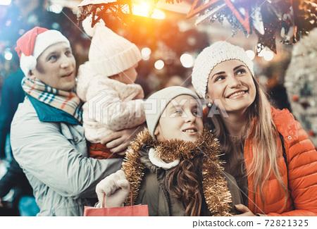 Family spending time at Christmas fair 72821325